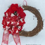 grapevine wreath decorated for Valentine's Day with red silk roses